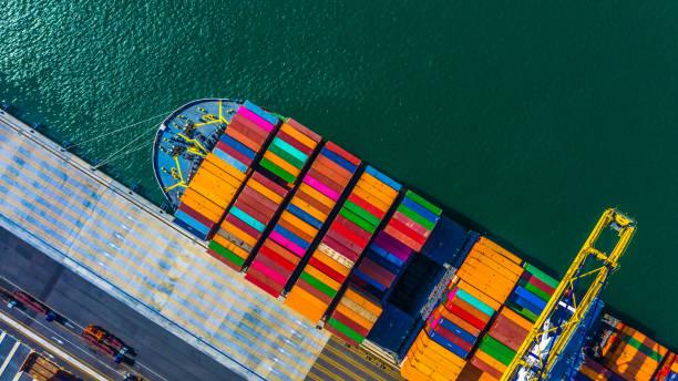集裝箱貨物貨輪與工作起重機橋在集裝箱碼頭卸貨, 在深海港口鳥頂視圖集裝箱船。 - 船運 個照片及圖片檔