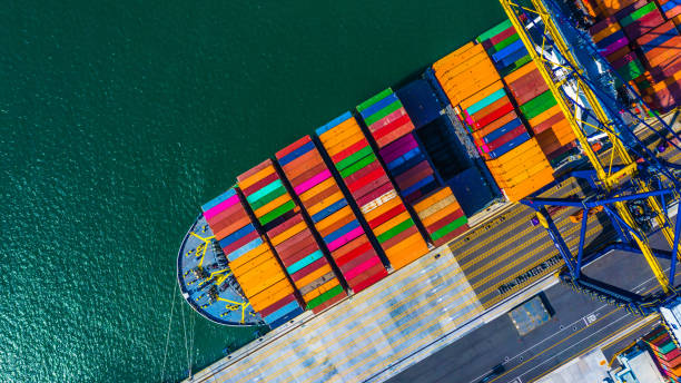 Container cargo freight ship with working crane bridge discharge at container terminal, Aerial top view container ship at deep sea port. stock photo