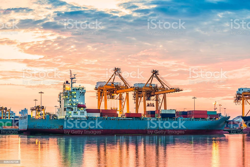Container Cargo freight ship with working crane bridge in shipya stock photo