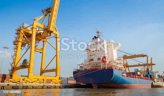 Container Cargo freight ship with working crane bridge in shipyard in singapore