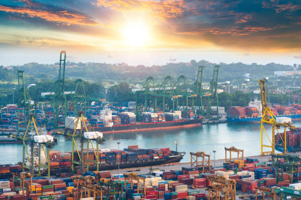 Container Cargo freight ship with working crane bridge in shipyard in singapore stock photo