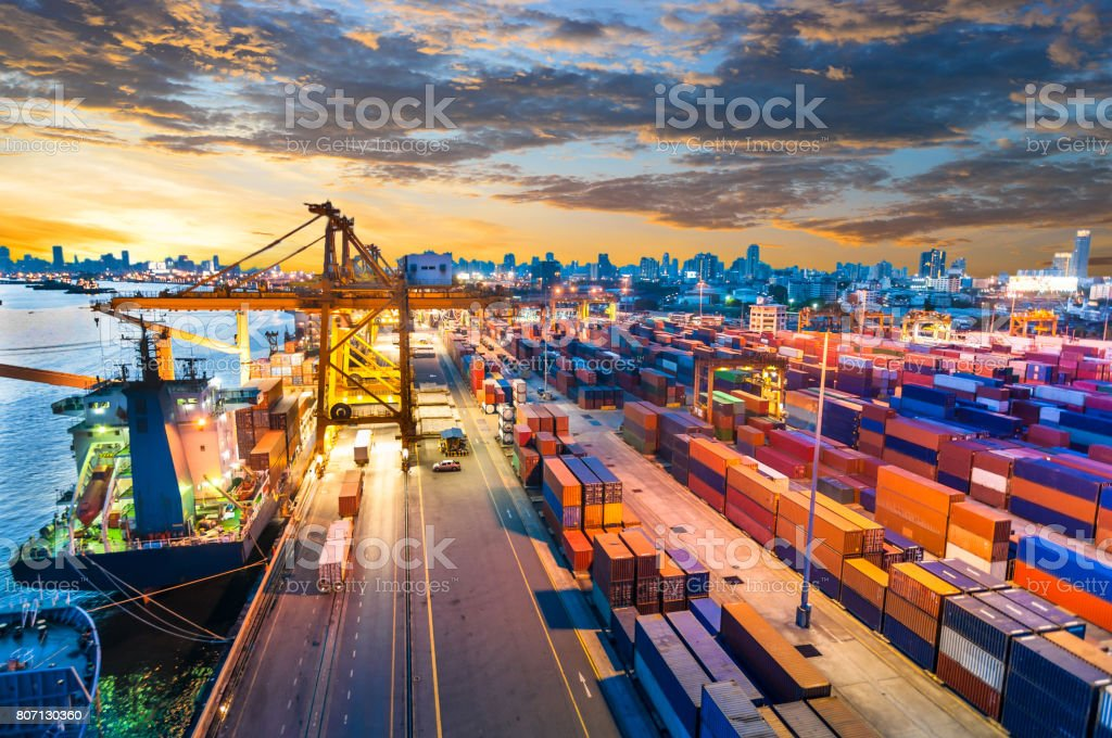 Container Cargo freight ship with working crane bridge in shipyard stock photo