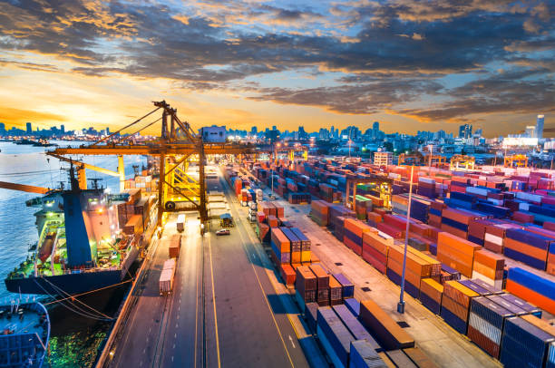 container cargo freight ship with working crane bridge in shipyard - distribution warehouse stock photos and pictures