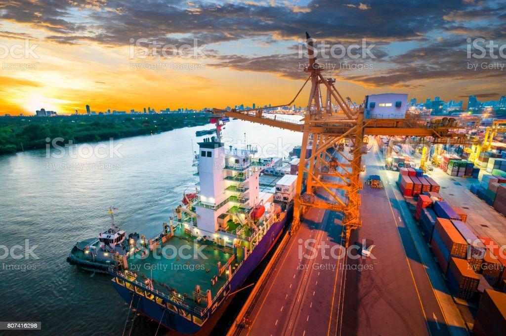 Envase de transporte de carga por barco con la grúa de trabajo puente en shipyard - foto de stock