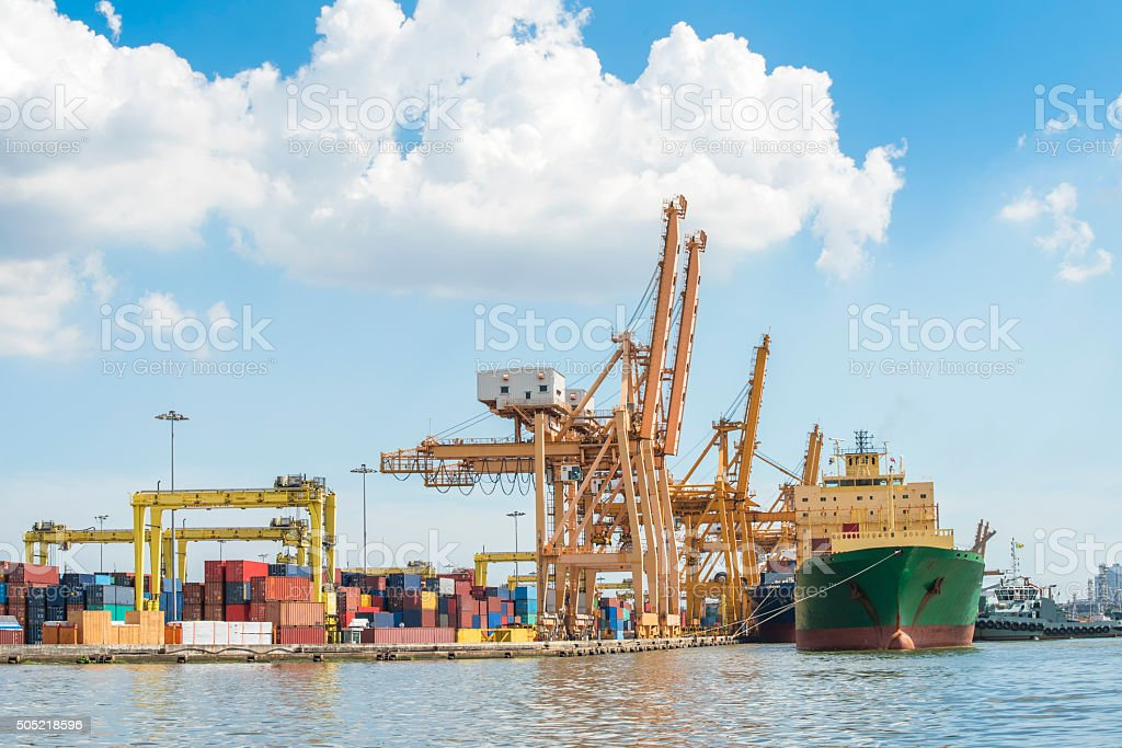 Container Cargo freight ship with working crane loading bridge stock photo