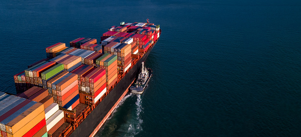 Container cargo ship business commercial trade import export logistic transportation container box oversea worldwide by container vessel boat freight shipping maritime with tugboat.