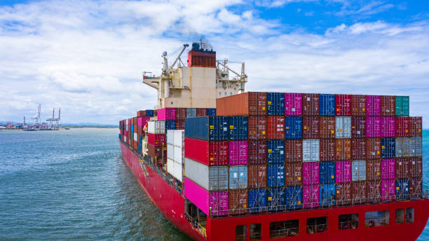 Container cargo ship carrying container for business freight import and export, Aerial view container ship arriving in commercial port. Container cargo ship carrying container for business freight import and export, Aerial view container ship arriving in commercial port. carrying stock pictures, royalty-free photos & images