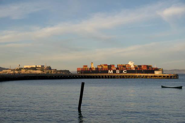 Container Cargo Ship entering San Francisco Bay and Alcatraz Island during sunset stock photo