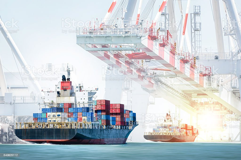 Container cargo ship entering the port with harbor crane background stock photo