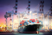 Container Cargo ship with ports crane bridge in harbor for logistic import export background and transport industry.