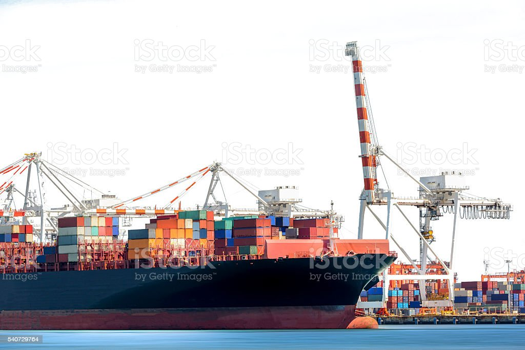 Container Cargo Ship with working crane bridge in shipyard isolated stock photo
