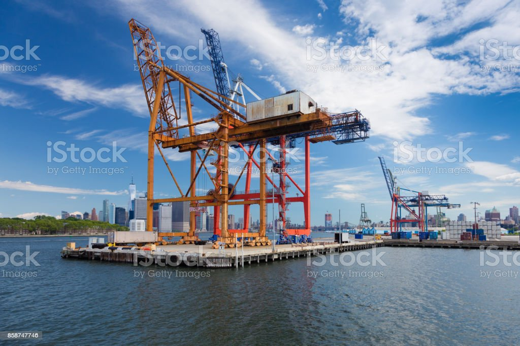 Container Crane at Red Hook Port with Governors Island and Manhattan Financial District in Background and Cloudy Blue Sky, Brooklyn, New York. stock photo