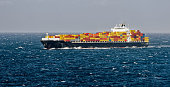Container freighter ship sailing in stormy ocean