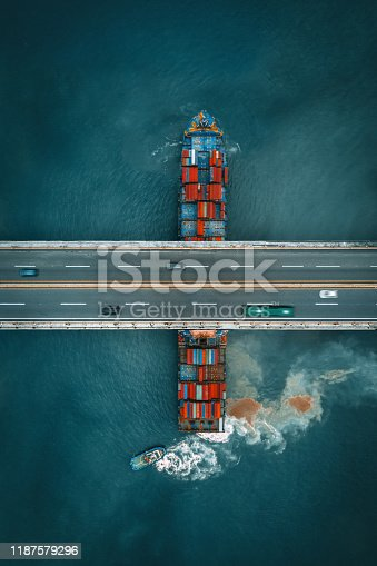 Container freight ship sailing under a road bridge