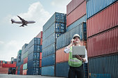 istock Container Logistics Shipping Management for Transportation Industry, Transport Engineer Manager Communication Via Walkie-Talkie to Worker in Containers Shipyard. Business Cargo Ship Factory Logistic. 1225570315