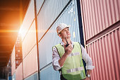 istock Container Logistics Shipping Management of Transportation Industry, Transport Engineer Control Via Walkie-Talkie to Worker in Containers Shipyard. Business Cargo Ship Import/Export Factory Logistic. 1227353907