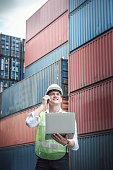 istock Container Logistics Shipping Management of Transportation Industry, Transport Engineer Managing Control Via Computer Laptop in Containers Shipyard. Business Cargo Ship Import/Export Factory Logistic. 1257144500