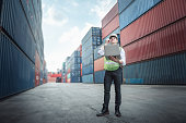istock Container Logistics Shipping Management of Transportation Industry, Transport Engineer Managing Control Via Computer Laptop in Containers Shipyard. Business Cargo Ship Import/Export Factory Logistic. 1257144673