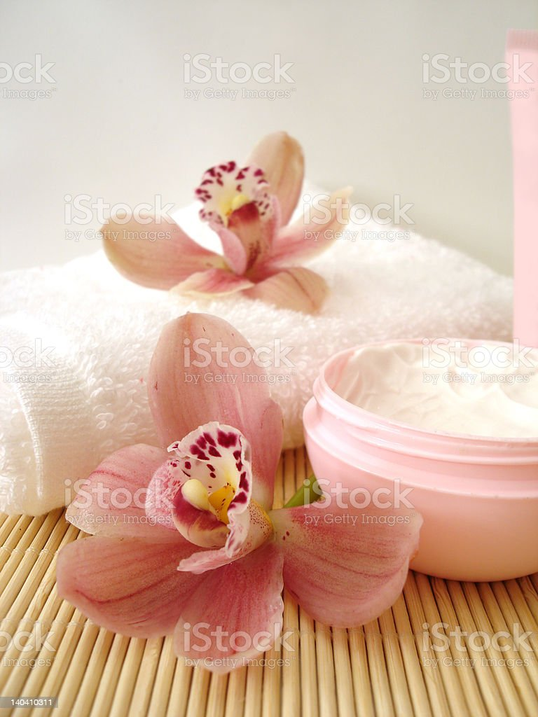 container of cosmetic moisturizing cream with pink orchids and towel royalty-free stock photo