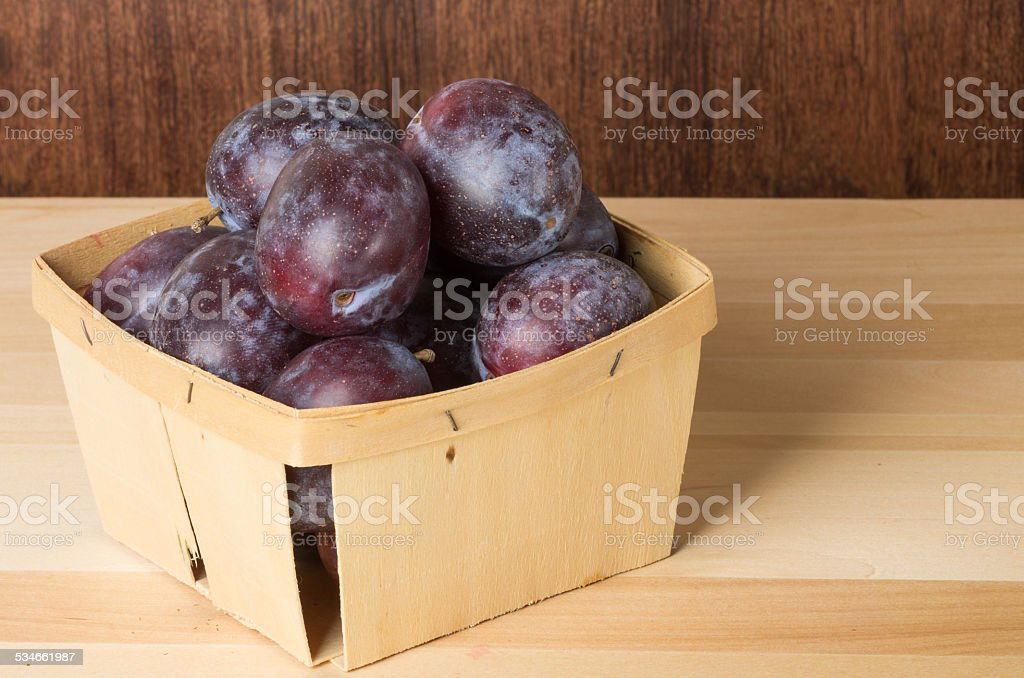 Container of prune plums on table stock photo