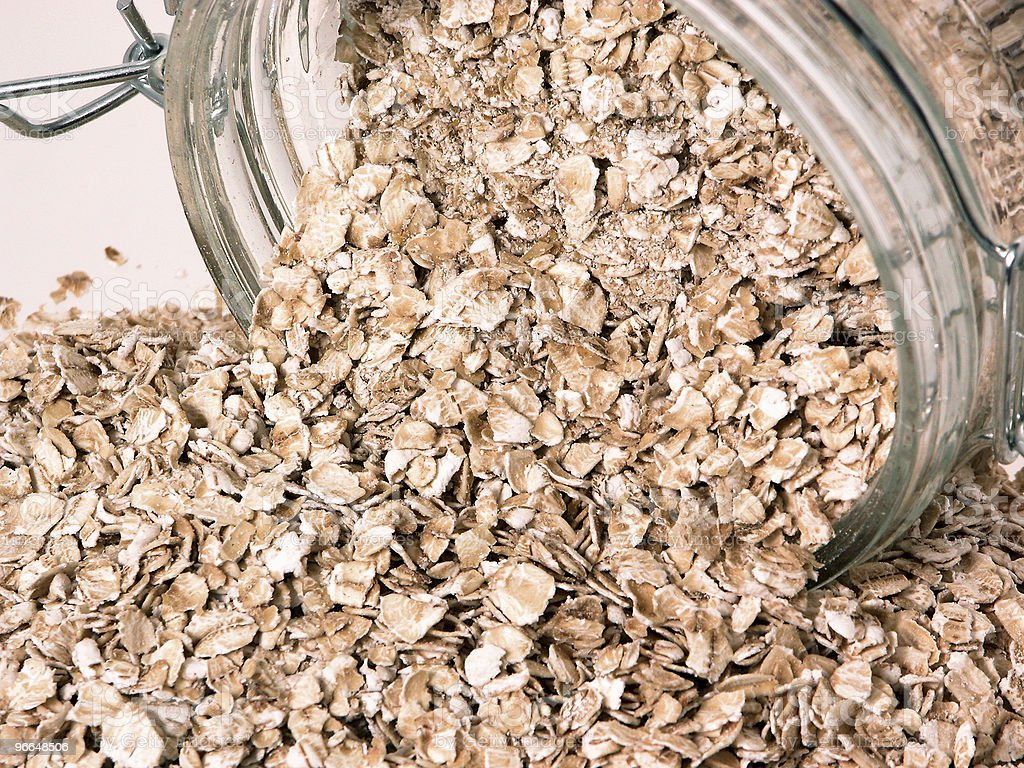 Container of Spilt Raw Oats on Table royalty-free stock photo