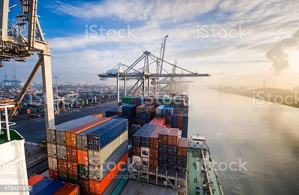 Sunrise in busy container terminal in Rotterdam, Netherlands.