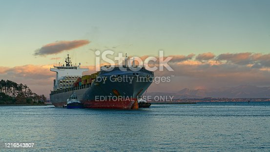 Nelson, Nelson/New Zealand - June 16, 2019: Two pilot vessels nudge a container ship through the cut and into Port Nelson, New Zealand.