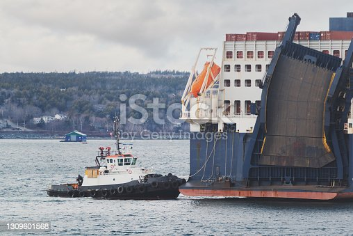 istock Container Ship Assisted By Tugboat 1309601868