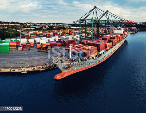Drone view of a container ship in loading/unloading at port.