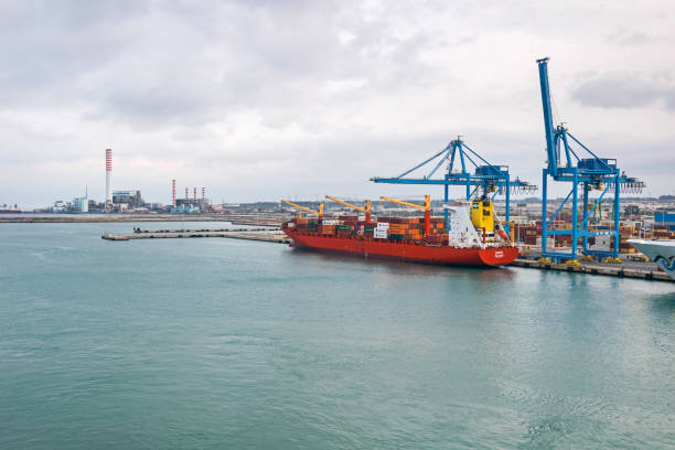 Container Ship Barry Majuro loading containers at the port of Civitavecchia Civitavecchia, Italy -  October 30, 2019: Container ship Barry Majuro loading containers with rail cranes at the port of Civitavecchia deadweight stock pictures, royalty-free photos & images