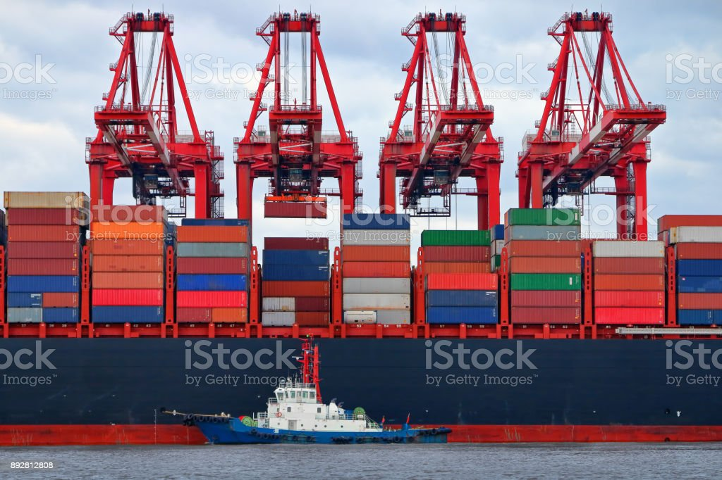 Container ship being loaded with cranes stock photo