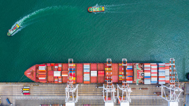 Container ship carrying container in import export business logistic and transportation of international by container ship in the open sea. stock photo