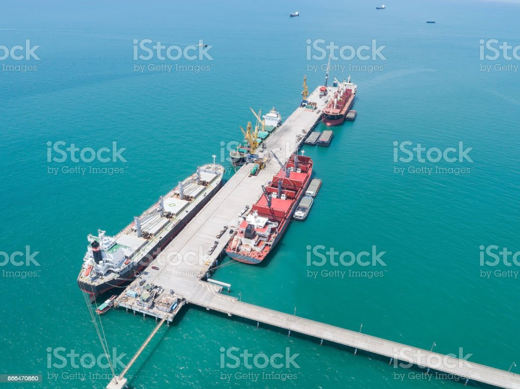container ship commercial vessel alongside in port for loading and discharging containers services in maritime transports in World wide logistics stock photo