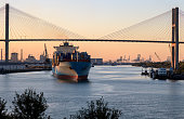 At dusk a Container Ship on the Savannah River is Departing from the Port of Savannah heading toward the Atlantic Ocean.