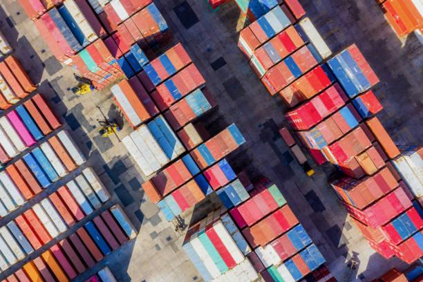 Containerschiff im Export- und Importgeschäft und in der Logistik. Transport von Fracht zum Hafen mit dem Kran. Wassertransport International. Luftbild – Foto