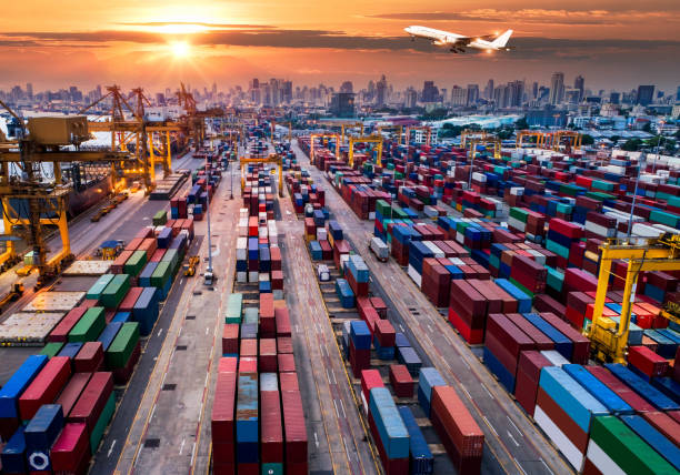 Porte-conteneurs en import export et entreprise de logistique. Port de commerce. Expédition, cargo port et avion Cargo avec pont roulant au chantier naval de travail au lever du soleil, logistique import export et transport de fond de l'industrie - Photo