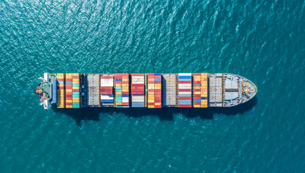 container ship in import export and business logistic.By crane ,Trade Port , Shipping.cargo to harbor.Aerial view.Water transport.International.Shell Marine.Top view. stock photo