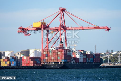 Perth, Australia - December 10, 2015: Container ship Margaret River Bridge in the Harbor of Fremantle. Port crane loads and unloads containers from the ship.