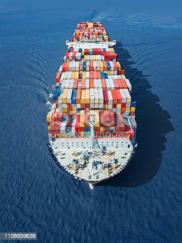 Front view of a fully loaded container ship in the blue sea