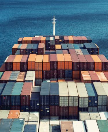 Looking down over the deck of a container ship headed for ports overseas.  Stitched images.