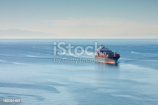 Distant aerial photo of a loaded container ship at sea.
