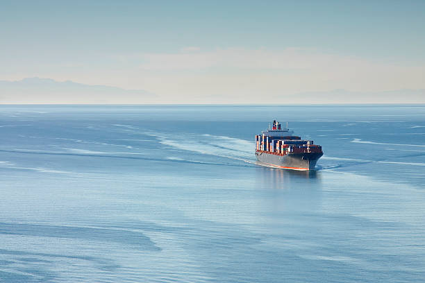 Container Ship Distant aerial photo of a loaded container ship at sea. container ship stock pictures, royalty-free photos & images