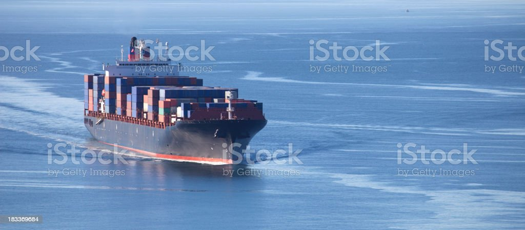 Container Ship Large cargo container ship sailing into port. Aerial View Stock Photo