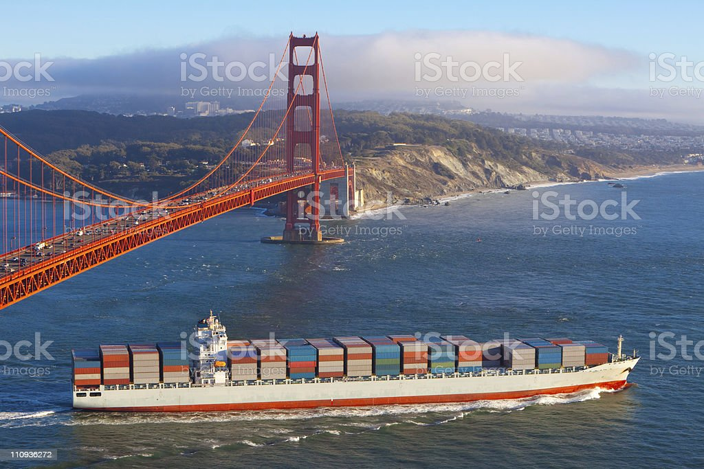 Container ship sailing under Golden Gate bridge out to sea royalty-free stock photo