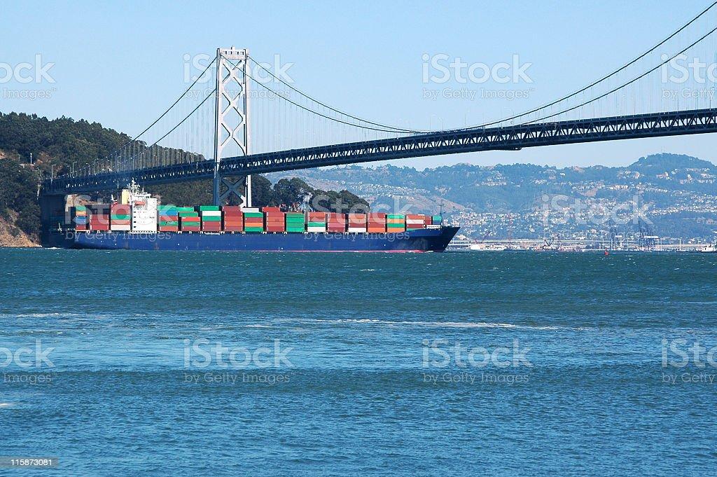 container ship sailing under the Bay Bridge, San Francisco, California royalty-free stock photo