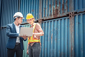 istock Container Shipping Logistics Engineering of Import/Export Transportation Industry, Transport Engineers Teamwork Controlling Management Containers Box on Laptop at Port Ship Loading Dock. Business Team 1247787059