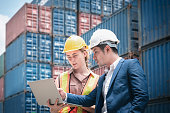 istock Container Shipping Logistics Engineering of Import/Export Transportation Industry, Transport Engineers Teamwork Controlling Management Containers Box on Laptop at Port Ship Loading Dock. Business Team 1253379685