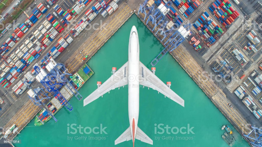 Container ships and transport aircraft in the export and import business and logistics international goods. Shipping cargo to harbor by crane. Aerial view and top view. stock photo