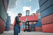 istock Container Supervisor Control Import/Export While Inspecting Containers Box in Warehouse Storage Distribution. Container Logistics Shipping Controlling of Transportation Industry, Cargo Ship Factory 1281274977