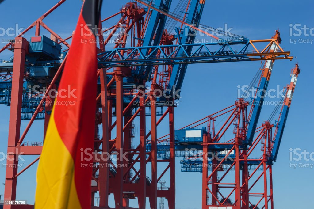 German flag in front of container quay and container ships in the...